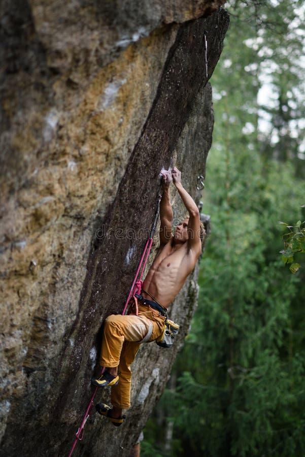 O montanhista de rocha masculino esforça-se para alcançar seu aperto seguinte em um penhasco íngreme Esporte extremo imagens de stock royalty free