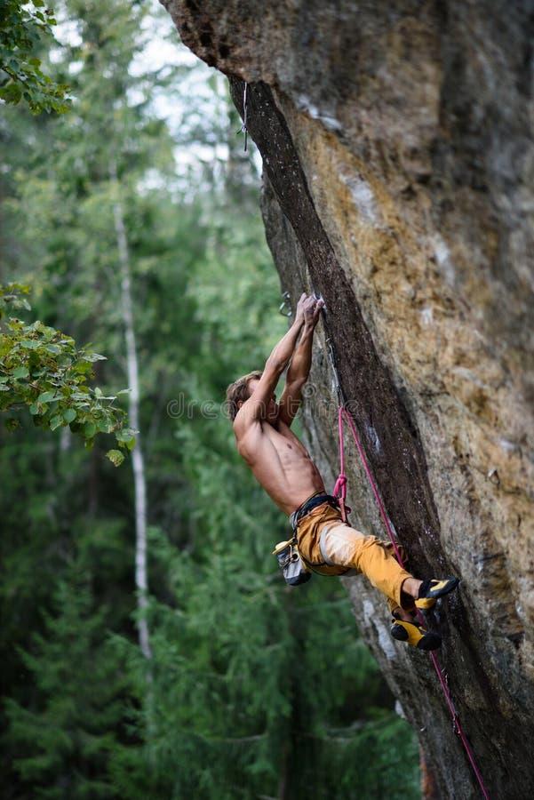O montanhista de rocha masculino esforça-se para alcançar seu aperto seguinte em um penhasco íngreme Esporte extremo imagem de stock royalty free