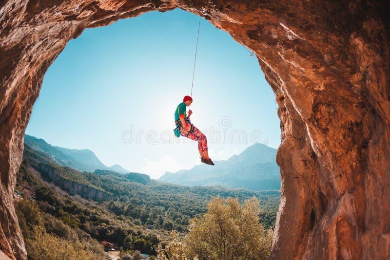 O montanhista está pendurando em uma corda fotografia de stock
