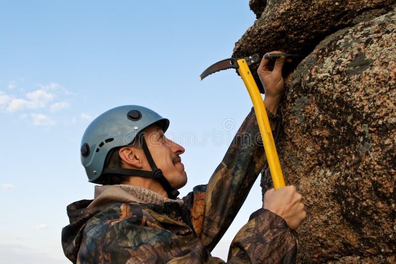 O montanhista martela no gancho na rocha imagens de stock