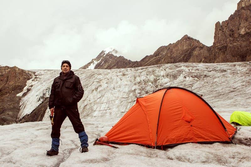 O montanhista que está a barraca próxima na geleira foto de stock royalty free