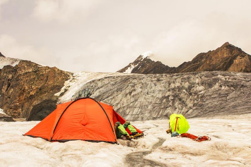 O montanhista tem um resto que encontra-se na barraca na geleira imagens de stock royalty free