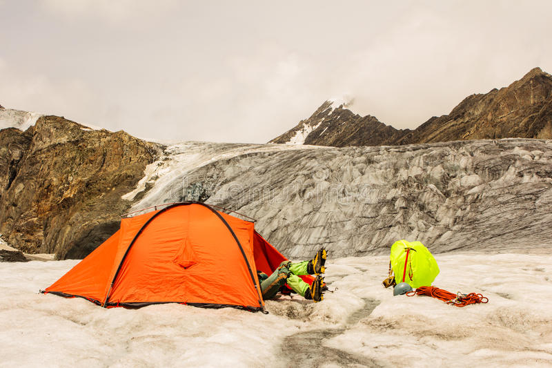 O montanhista tem um resto que encontra-se na barraca na geleira fotografia de stock royalty free