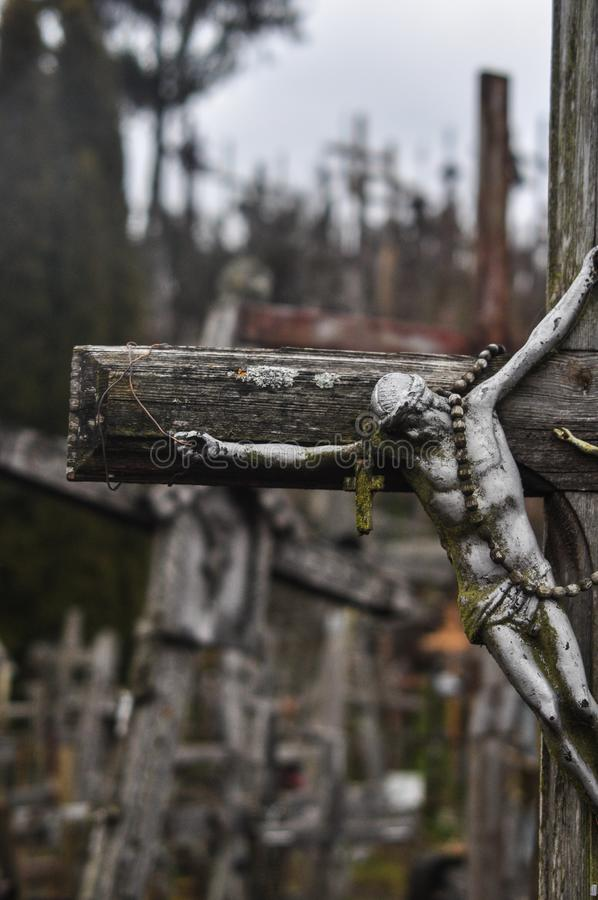 O monte das cruzes em Lituânia com um tiro dos detail's de uma única cruz com uma figura de Jesus destacou foto de stock