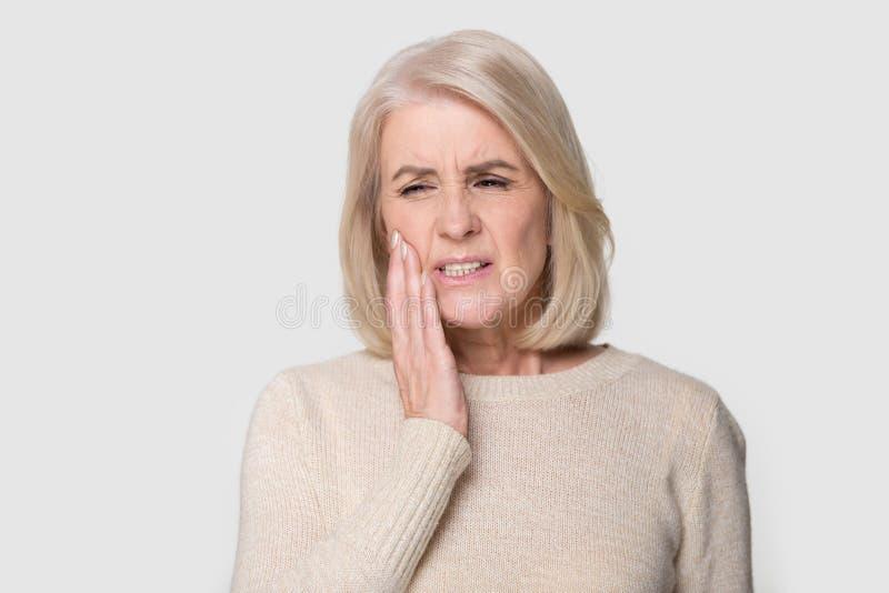 O mordente maduro dos toques da mulher do retrato do Headshot sofre da dor do dente imagens de stock royalty free