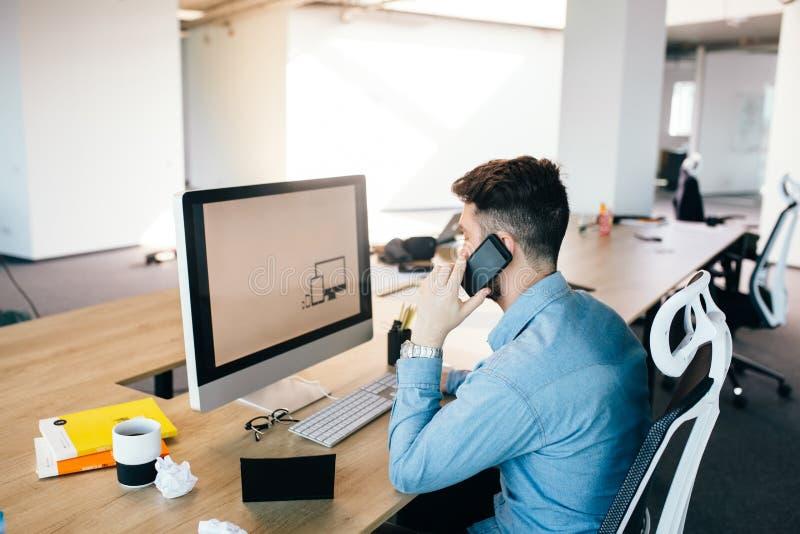 O moreno novo está trabalhando com um computador e está falando no telefone em seu desktop no escritório Veste a camisa azul foto de stock royalty free