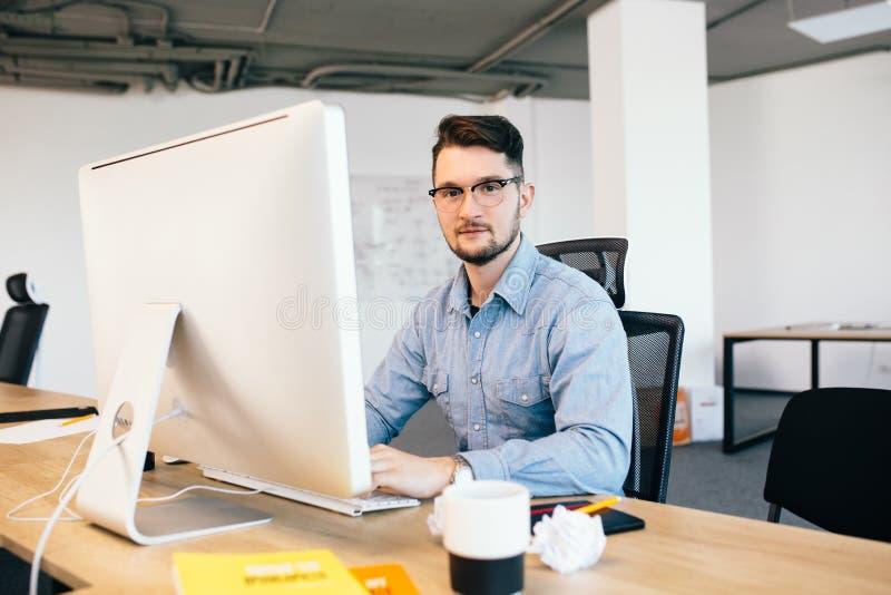 O moreno novo nos glasess e em uma camisa azul está trabalhando com um computador em seu desktop no escritório Está sorrindo a fotografia de stock