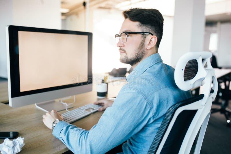O moreno novo nos vidros está trabalhando com um computador em seu desktop no escritório Veste a camisa azul e olha a imagens de stock royalty free