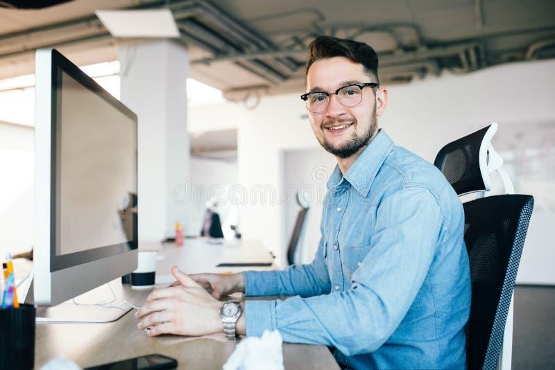 O moreno novo nos vidros está trabalhando com um computador em seu desktop no escritório Veste a camisa azul e sorri a fotografia de stock royalty free