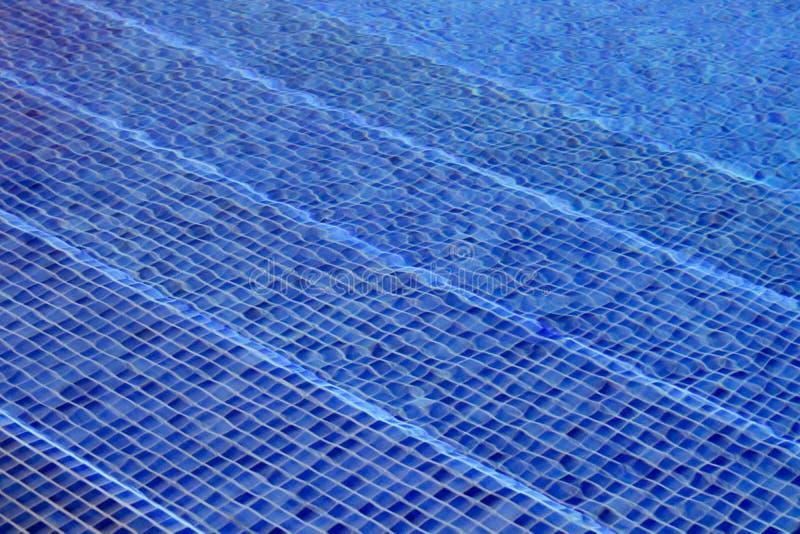 O mosaico azul telhou as etapas vistas através da água - imagem da piscina foto de stock