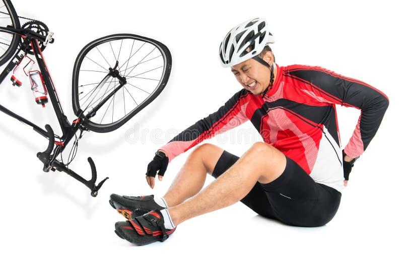 O motociclista asiático caiu para baixo da bicicleta fotografia de stock
