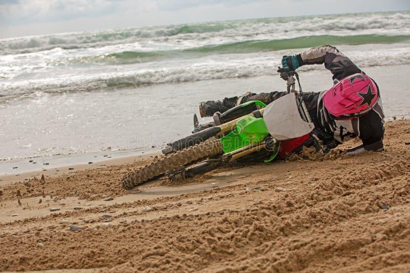 O motociclista caiu em uma motocicleta na praia contra o contexto do mar fotografia de stock