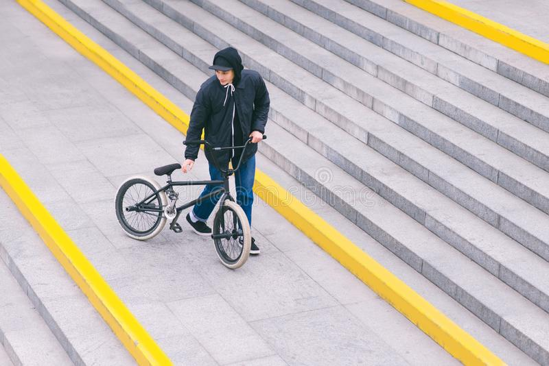 O motociclista de BMX está estando nas escadas e está olhando de lado a lado Vista superior Caminhada com uma bicicleta Cultura d fotografia de stock