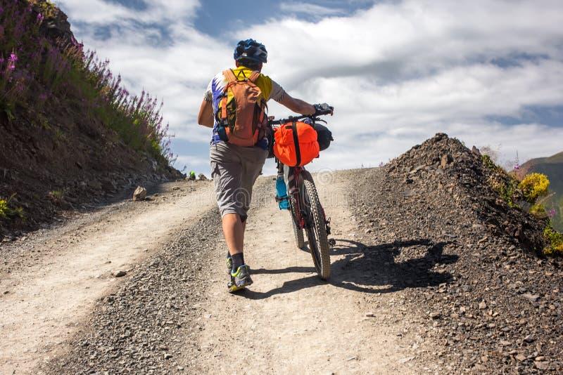 O motociclista empurra sua bicicleta acima em montanhas de Cáucaso altas imagens de stock royalty free