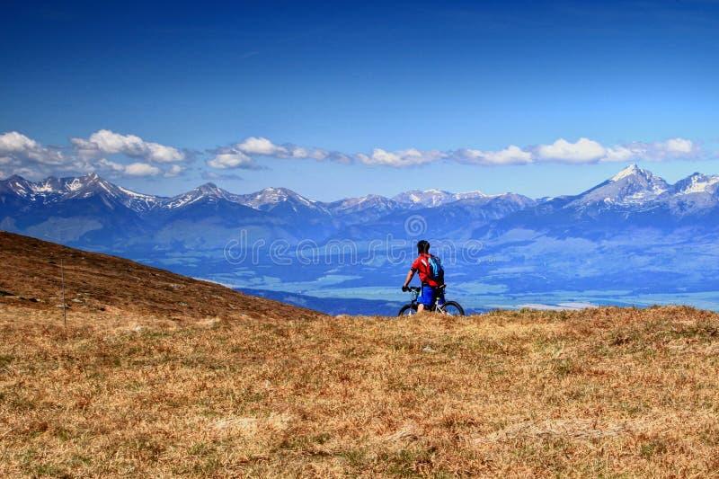 O motociclista monta um Mountain bike antes dos picos nevado Eslováquia de Tatra imagem de stock