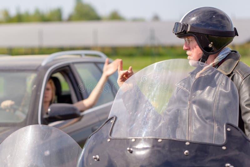 O motociclista mostra seu dedo médio a um motorista fotos de stock