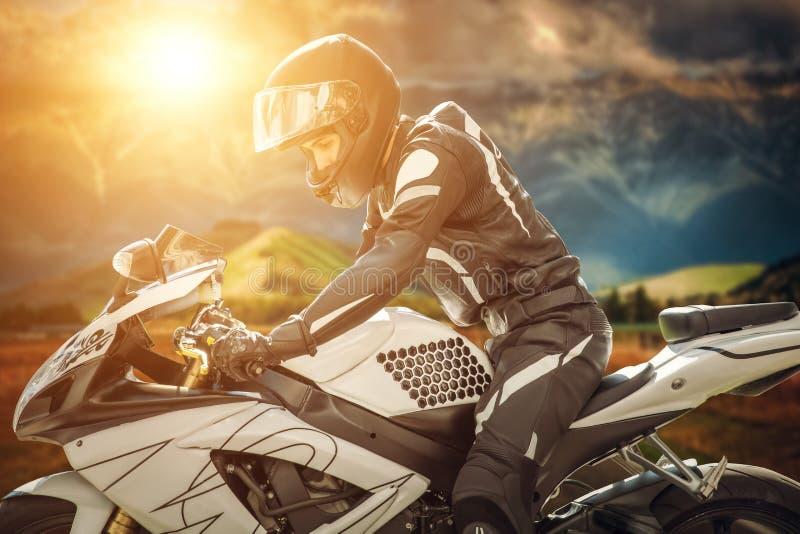 O motociclista na bicicleta do esporte está na borda das montanhas no fundo de um por do sol brilhante fotos de stock royalty free