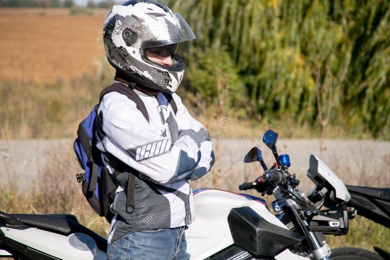 O motociclista no capacete em uma motocicleta Viagem a uma motocicleta O motociclista está na estrada foto de stock royalty free