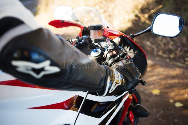O motociclista senta-se em uma motocicleta com luvas e capacete fotos de stock