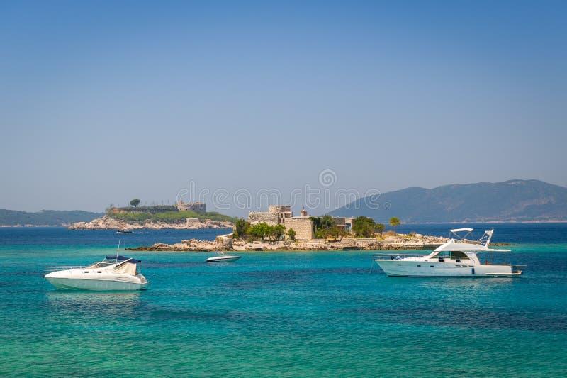 O motor luxuoso yachts na âncora perto da fortaleza velha em uma ilha pequena imagem de stock