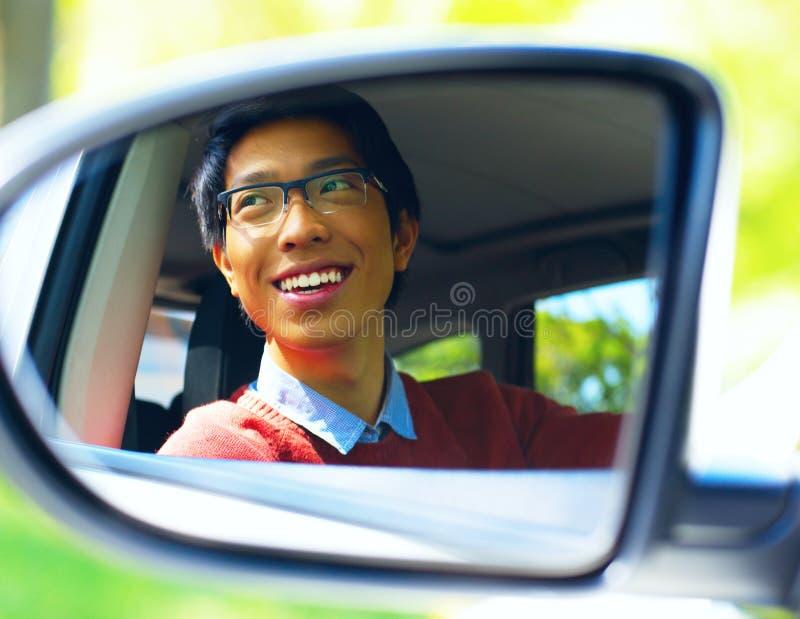 O motorista asiático é refletido no espelho foto de stock royalty free
