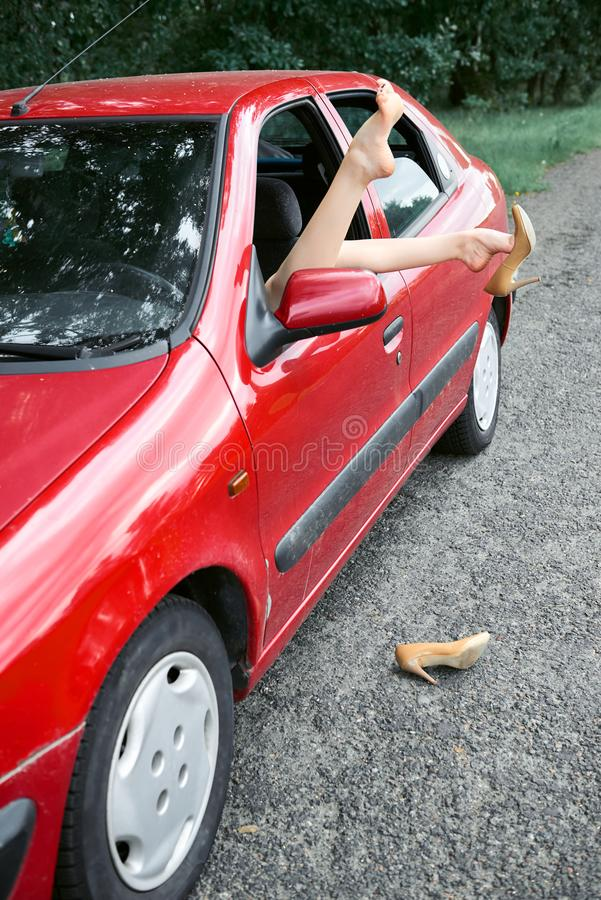 O motorista da jovem mulher que descansa em um carro vermelho, pôs seus pés sobre a janela de carro, conceito feliz do curso, mul imagens de stock