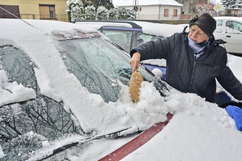 O motorista da mulher limpa a neve do carro fotos de stock