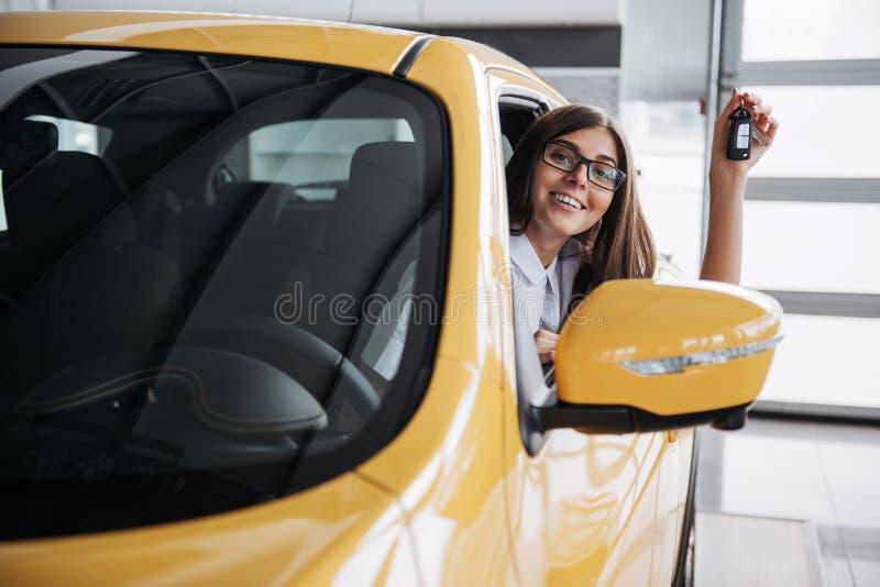 O motorista da mulher que sorri mostrando chaves novas do carro foto de stock royalty free