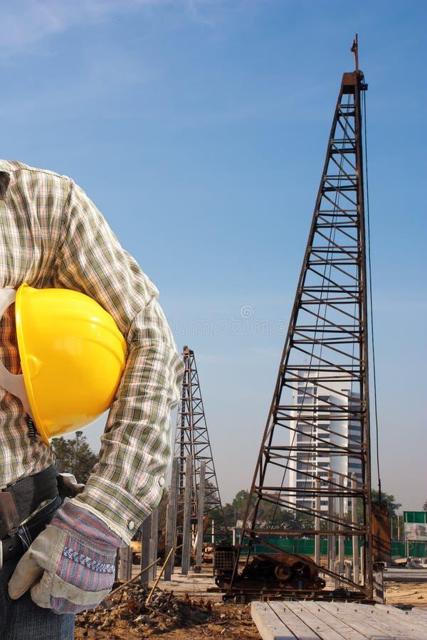 O motorista de pilha trabalha para ajustar pilhas do concreto pré-fabricado em um constructi foto de stock royalty free