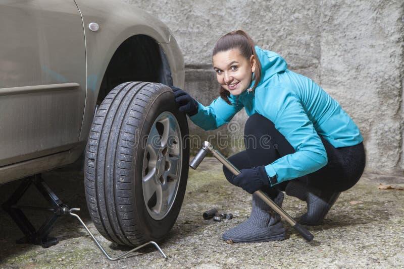 O motorista de sorriso novo da mulher muda pneumáticos do carro fotos de stock royalty free