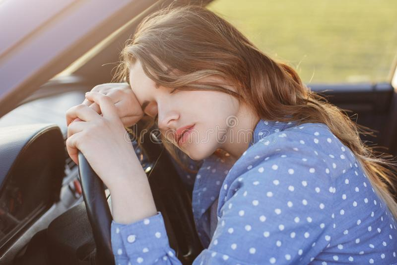 O motorista fêmea sobrecarregado esgotado pode carro da movimentação do ` t any more, sestas na roda, sente sonolento e cansado,  foto de stock