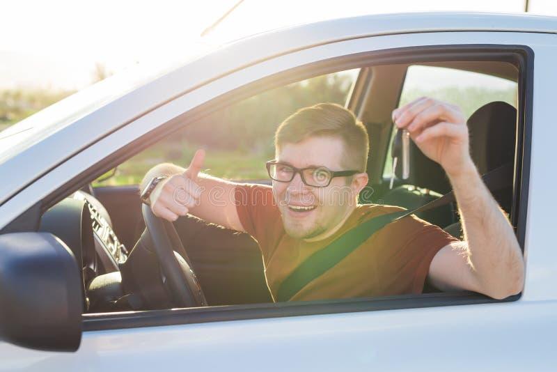 O motorista novo que mostram chaves do carro e os polegares levantam feliz Homem que guarda a chave do carro para o automóvel nov fotografia de stock royalty free
