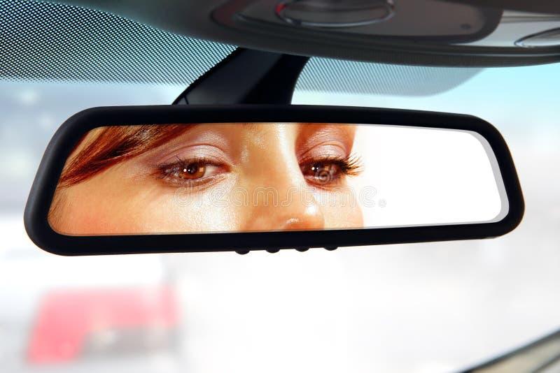 O motorista olha ao espelho retrovisor fotos de stock royalty free