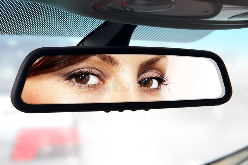 O motorista olha ao espelho retrovisor fotografia de stock royalty free
