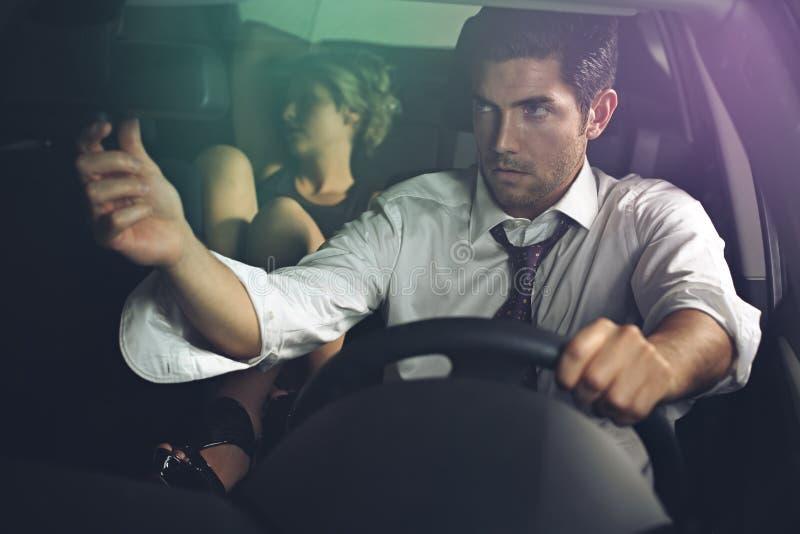 O motorista olha a mulher bonita no espelho retrovisor imagens de stock