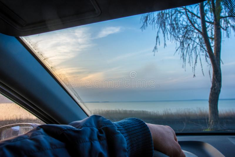 O motorista senta-se no carro e olha-se para fora a janela Conduziu acima ao lago no por do sol ou no nascer do sol imagens de stock royalty free
