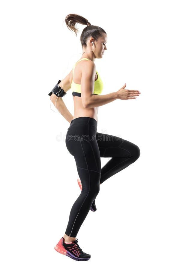 O movimento congelado do corredor atlético fêmea do ajuste que faz joelhos altos aquece o exercício foto de stock