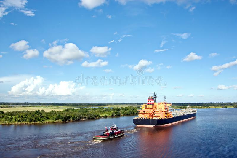 O movimento de navios mercantes e de reboquees do mar à entrada e à saída do porto Beaumont, Texas foto de stock
