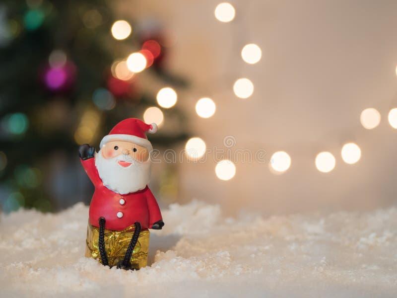 O movimento de Santa senta o giftbox no fundo do bokeh da neve imagens de stock royalty free