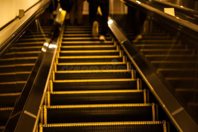 O movimento do vintage borrou a pressa do homem que anda acima da escada rolante durante as horas de ponta na área urbana do shop imagem de stock