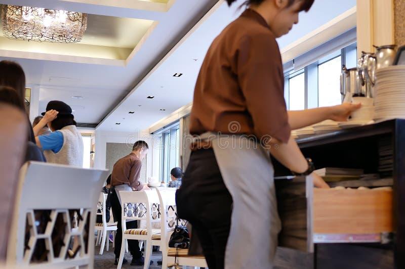 O movimento dos povos que comem alimentos e o trabalhador que classifica a placa e rolam para fora dentro do restaurante imagem de stock