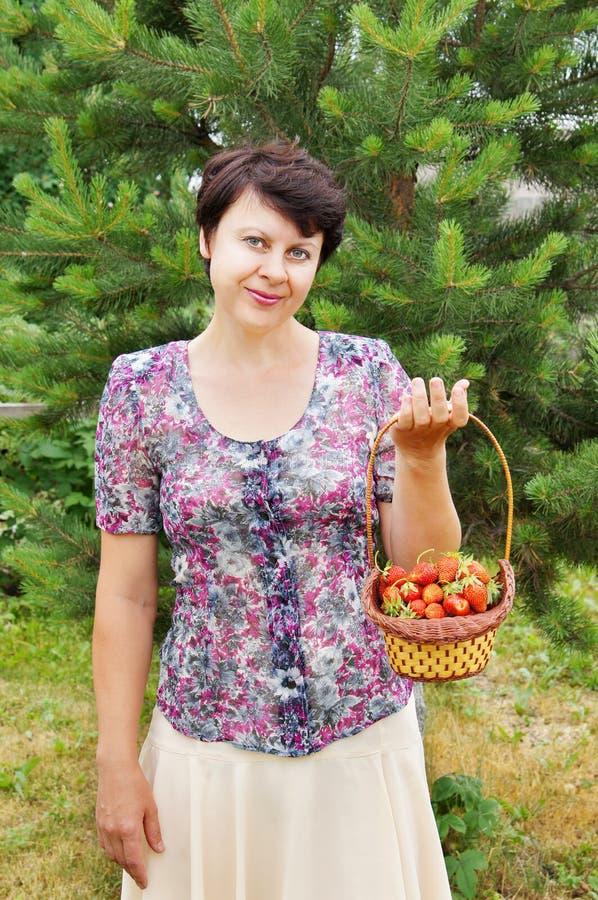 o Mulher-jardineiro prende uma cesta com morango imagens de stock