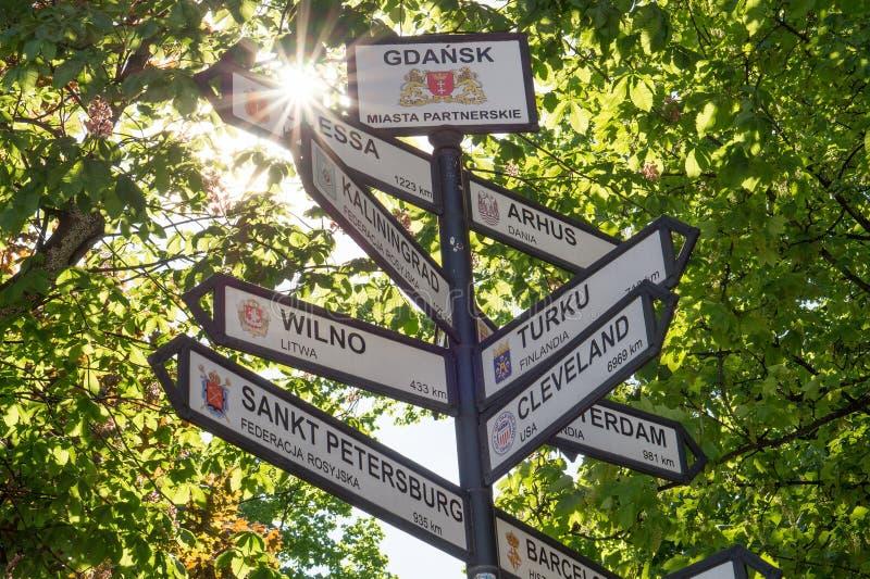 O multi sentido assina dentro Gdansk que mostra a distância às cidades do gêmeo do ` s da cidade e às cidades de irmã imagem de stock
