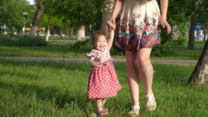 O Mum anda no parque no gramado com criança pequena, mamã ensina para andar pouca filha, criança guarda a mão de sua mãe fotografia de stock