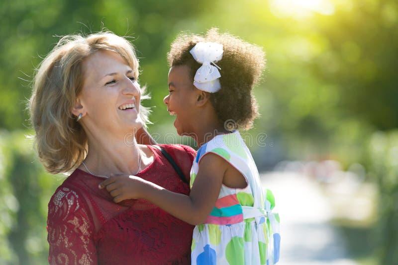 O mum branco e a filha preta estão rindo na rua imagem de stock royalty free