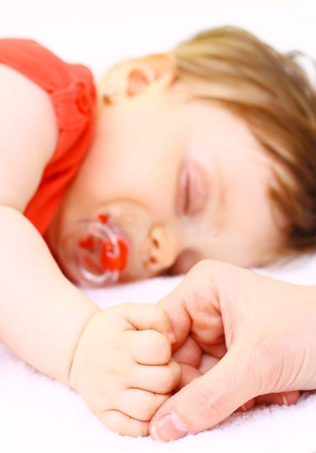 O Mum prende a mão o bebê pequeno imagem de stock royalty free