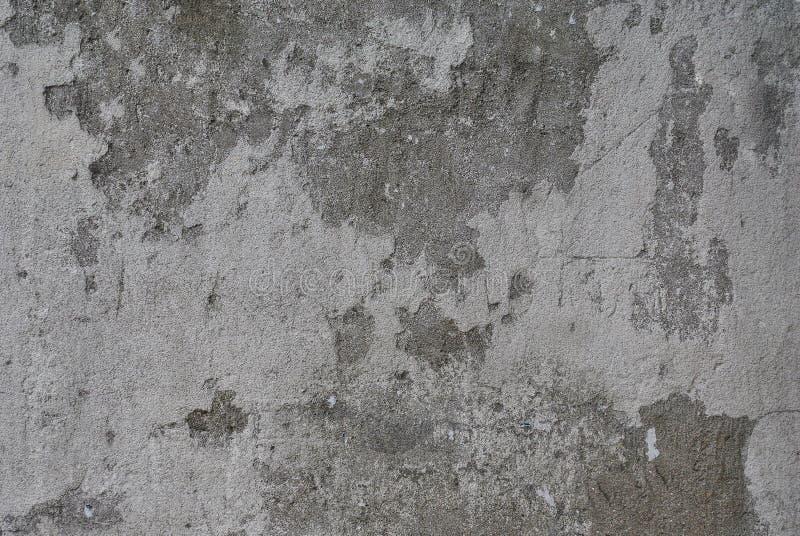 O muro de cimento e o emplastro cinzentos velhos permanecem nele foto de stock