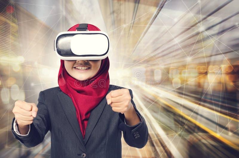 O muslimah novo profissional que vestem auriculares da realidade virtual e o ato gostam de conduzir sobre o fundo abstrato da exp fotografia de stock