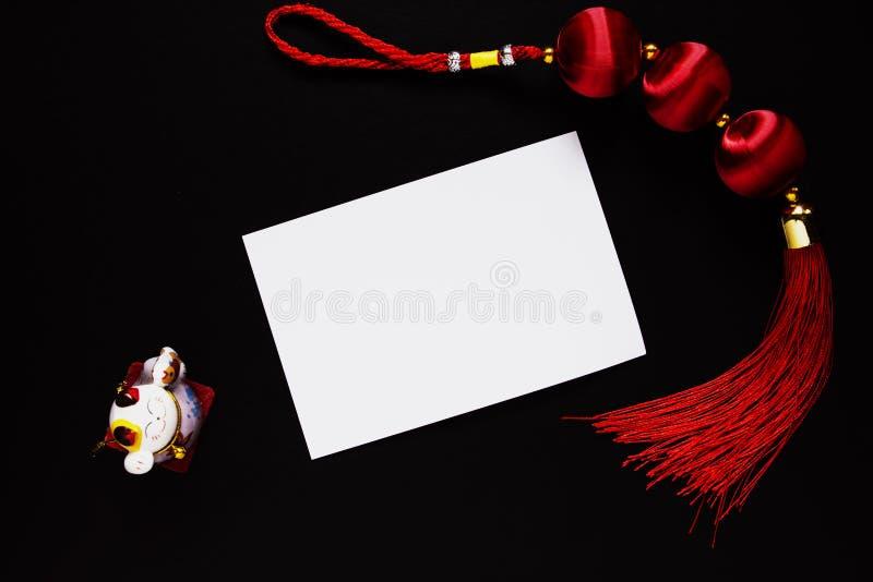 O nó, a estatueta afortunados chineses do gato do neko do maneki e esvaziam o cartão de papel no preto foto de stock