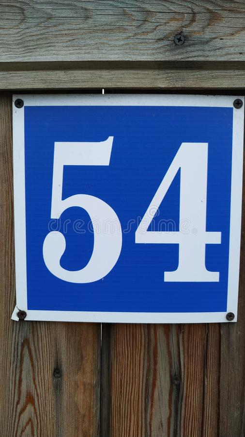 O número 54 é branco no quadro azul Close-up fotografia de stock